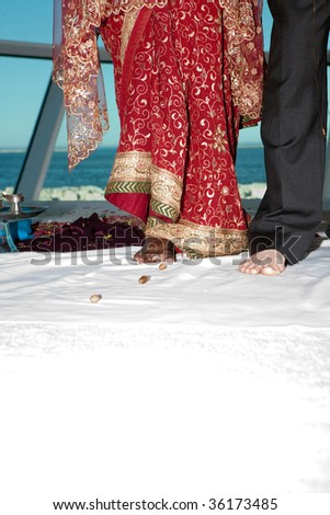 A bride and groom perform a series of steps as part of a traditional Hindu wedding ceremony