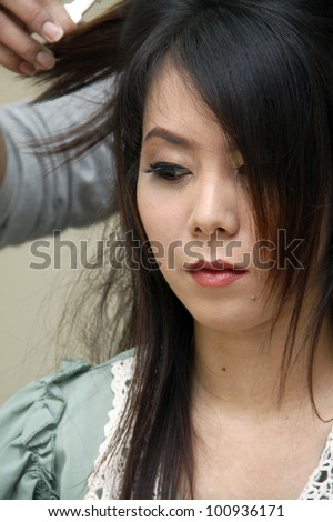 A bride having hair setup on her wedding day