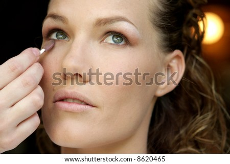 A bride having her makeup done on her wedding day