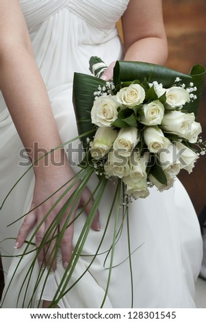 A bride holds her bouquet of white roses