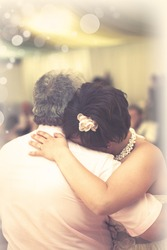 A bride hugs her father at the end of the father daughter dance at her wedding reception
