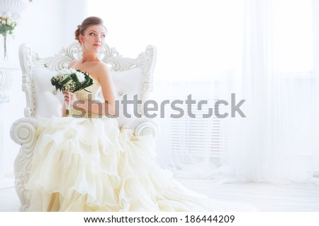A bride in a beautiful dress holding a bouquet of flowers and greenery. Wedding. wedding bouquet. Bride