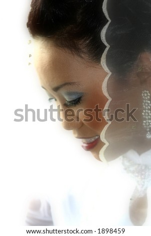 A bride in white after the application of her bridal make-up stands by the window.