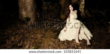 A bride sitting beneath a tree in dark woods