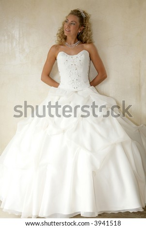 A bride standing against a wall in her gown