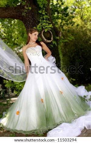 A bride standing under a tree in her wedding dress