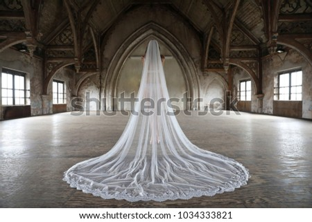 A bride stands in her white wedding dress in the church in front of the altar.