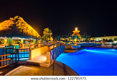 A bridge across swimming pool in a luxury caribbean resort at night, dawn time. Bahia Principe, Riviera Maya, Mexican Resort.