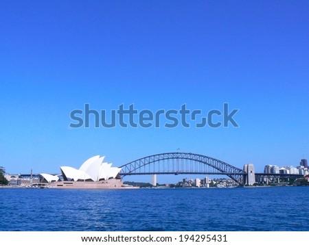 A bridge and opera house across the Sydney harbor.