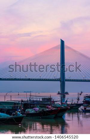 A bridge crosses the sea at sunrise and sunset in hainan, China.
