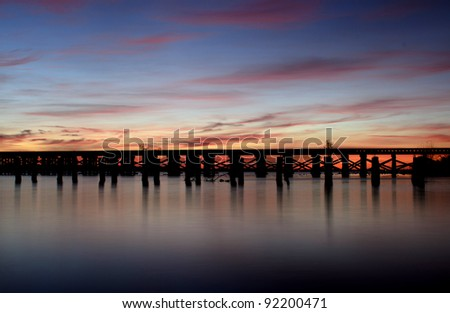 a bridge crossing a river before sunrise