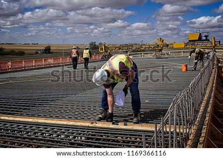 A bridge engineer inspecting spacing diameter and height of steel reinforcing bars with a tape measure on the bridge deck prior to pouring concrete on the reinforced deck supported by steel girders #1169366116