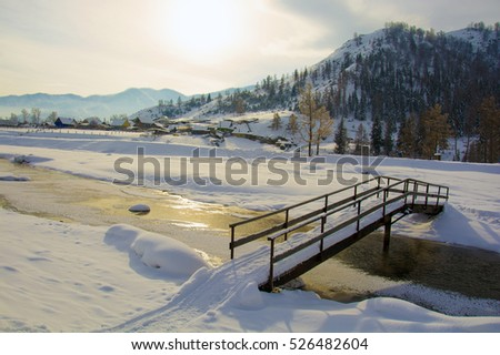 A bridge over a small creek, winter in the village, the ground under the snow.