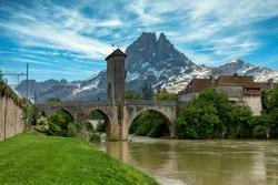 a bridge over river Gave de Pau in Orthez and Pic du midi Ossau - France