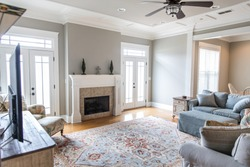 a bright and airy neutral beige gray living room den in a new construction house with a white and tiled fireplace as the main focal point as well as a decorative rug and lots of natural window light.