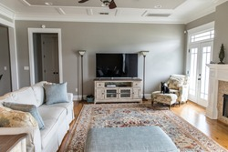 a bright and airy neutral beige living room den in a new construction house with a television and lots of natural light and furniture
