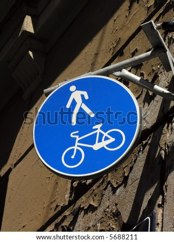 A bright blue bicycle and pedestrian warning sign against an old wall