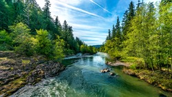 A bright blue river flowing through an Oregon forest as the sun begins to set in a hidden park along the scenic drive in southern Oregon, northern California border.
