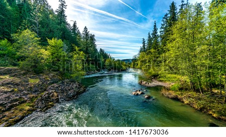 A bright blue river flowing through an Oregon forest as the sun begins to set in a hidden park along the scenic drive in southern Oregon, northern California border. Photo stock ©
