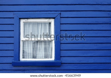 A bright blue wooden wall with a small white-framed window