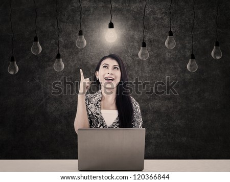 A bright business woman with light bulbs and a laptop sitting in front of blackboard