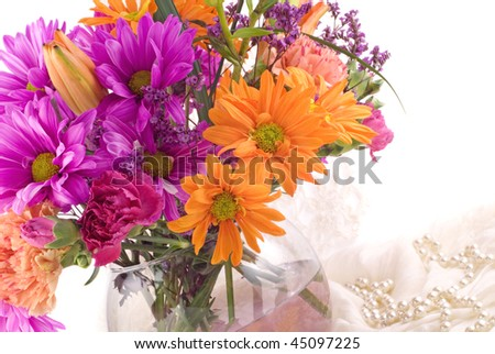 A bright cheery flower arrangement filled with pink and orange flowers on a white background with copy space, horizontal with selective focus, great for Mother's Day