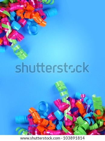 A bright colorful party streamer background. Birthday Swirls are in each corner on a blue background. Add your text to the copyspace area.