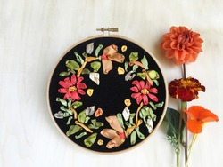 A bright floral ornament of orange, red and gold flowers is embroidered with satin ribbons on black velvet and a bouquet of autumn flowers next to it on a light wooden table. Flat lay, close-up