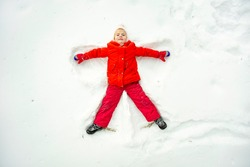 a bright girl in red clothes makes an angel in the snow lying top view on a winter day