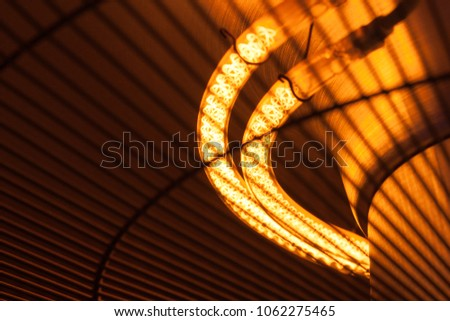 A bright hot filament spiral for a lamp or thermal heater glows orange and gives warmth #1062275465