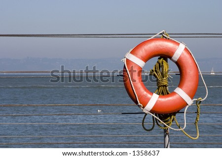 A bright orange lifesaver on the side of a ship.