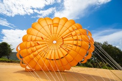 A bright orange parachute lies on the sand near the water to attract people to fly and look at the sea from a height.