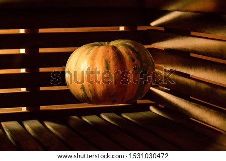 A bright orange pumpkin hangs in the air above a wooden surface against a background of walls made of wooden slats through which light breaks through. Mystical picture for the holiday Halloween