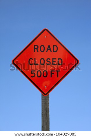 A bright orange road closed five hundred feet sign on a wood post against a blue sky.