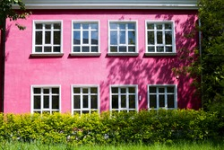 A bright pink building with large Windows surrounded by bright green trees and shrubs.