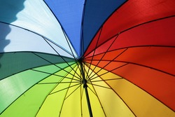 A bright rainbow colored umbrella in the afternoon. Symbol of different  yet beautiful thing in harmony.