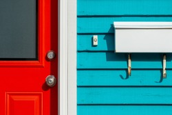 A bright red exterior door with a glass window, metal door knob and lock. The colorful teal blue horizontal wooden clapboard residential wall has a small white doorbell button and white letterbox.