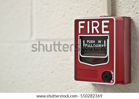 A Bright Red Fire Alarm Mounted on a Creamy Off White Cinder Block Wall