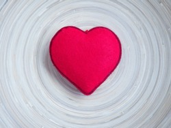 A bright red heart in the middle of wooden plate with free space around it. Ideal of holidays background, banner, backdrop, wallpaper or can be used for love concept.