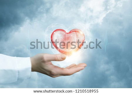 A bright red heart is flying above the doctor's hand with the slight cardiac waveforms behind at the cloudy background. #1210518955