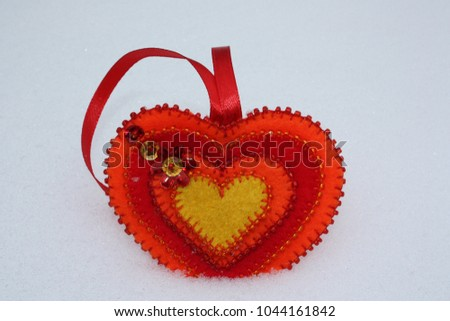 A bright red heart of hand-made, made of felt, beads and sequins in the middle of white snow. Romantic concept. Copy space. #1044161842