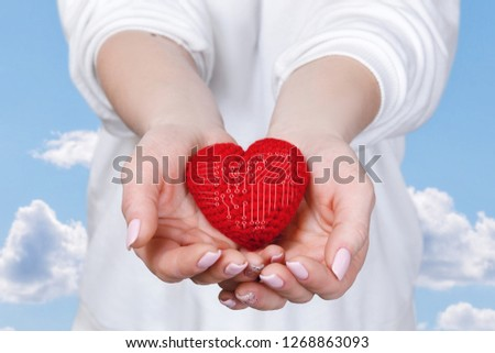 A bright red heart with a micro circuit system inside is laying in the woman 's palms at the cloudy blue sky background. The concept is the life mechanism working principle. #1268863093