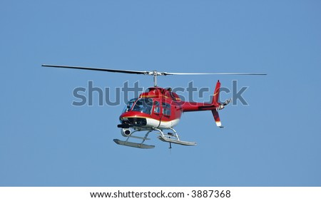 A bright red helicopter with a camera at a Fleet Week Air Show in 2006. A little motion blur on rotor blades