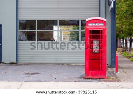 A bright red telephone booth sits abandoned on a street corner.