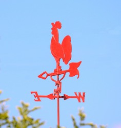 A bright red weathercock isolated against a blue sky
