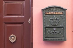 A bright retro looking green mailbox, or letterbox, affixed to the exterior wall of a pink house. There's a brown door with gold door knob