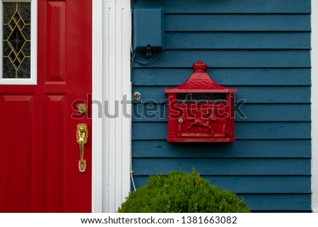 A bright retro looking red mailbox, or letterbox, affixed to the exterior wall of a blue wooden house made of clapboard. There's a red door with gold door knob and white trim on the building.  #1381663082