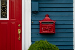 A bright retro looking red metal mailbox, or letterbox, affixed to the exterior wall of a blue wooden house made of clapboard. There's a red door with gold door knob and white trim on the building.