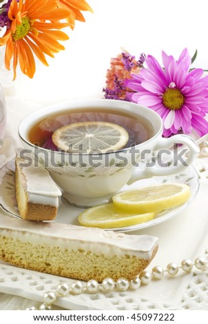 A bright sunny ladies tea party with fresh flowers, cup of tea, with fresh lemon slices on fine china with lemon biscotti cookies, vertical with copy space, perfect for Mother's Day