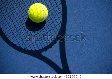 A bright tennis ball in a racket shadow with copyspace on the right